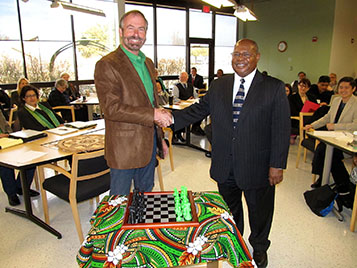 Provost Warren Burgren receives a digitally fabricated chess set from Dean Herman Totten and the COI faculty.
